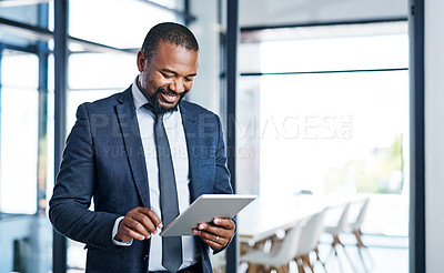 Buy stock photo Cropped shot of a handsome middle aged businessman using a digital tablet while standing in a modern office