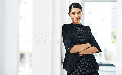 Buy stock photo Cropped portrait of an attractive young businesswoman standing with her arms folded in a modern office