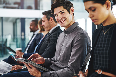 Buy stock photo Cropped shot of a handsome young businessman using a digital tablet while sitting in line for an interview in a modern office
