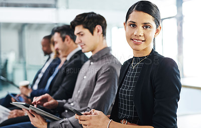 Buy stock photo Cropped shot of an attractive young businesswoman using a smartphone while sitting in line for an interview in a modern office