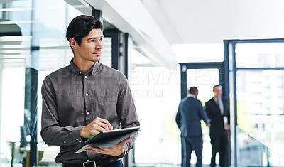 Buy stock photo Cropped shot of a handsome young businessman looking thoughtful while holding a digital tablet in a modern office