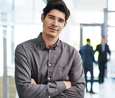 Buy stock photo Cropped portrait of a handsome young businessman standing with his arms folded in an office with his colleagues in the background