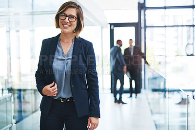 Buy stock photo Cropped portrait of an attractive young businesswoman smiling while standing in an office with her colleagues in the background