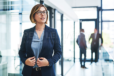 Buy stock photo Cropped shot of an attractive young businesswoman looking thoughtful in a modern office with her colleagues in the background