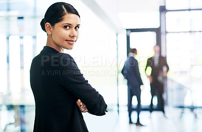 Buy stock photo Cropped portrait of an attractive young businesswoman standing with her arms folded in an office with her colleagues in the background