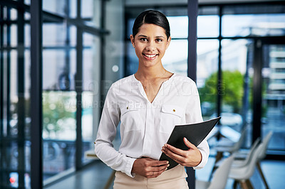 Buy stock photo Cropped portrait of an attractive young businesswoman smiling while holding a file in a modern office