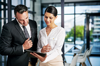 Buy stock photo Cropped shot of two businesspeople reading a file while standing in a modern office
