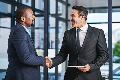 Buy stock photo Cropped shot of two handsome middle aged businessmen shaking hands in a modern office