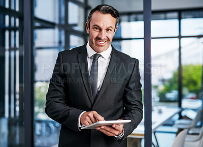 Buy stock photo Cropped portrait of a handsome mature businessman smiling while using a digital tablet in a modern office