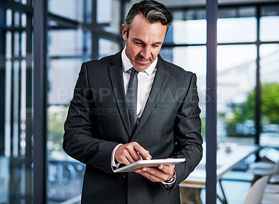 Buy stock photo Cropped shot of a handsome mature businessman using a digital tablet while standing in a modern office