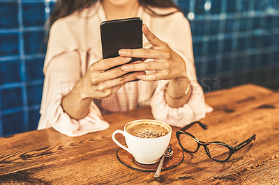 Buy stock photo Cropped shot of a woman using her cellphone while sitting in a coffee shop