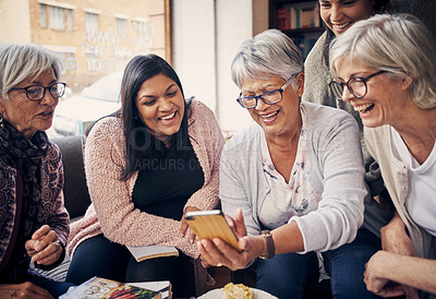 Buy stock photo Shot of a group of women using a smartphone together at their book club