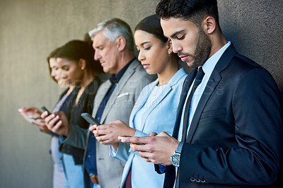 Buy stock photo Cropped shot of a diverse group of businesspeople standing together and using their cellphones