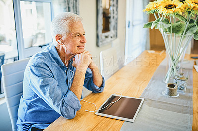 Buy stock photo Shot of a happy senior man wearing earphones and listening to music on his digital tablet at home