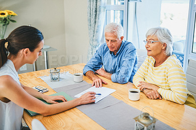 Buy stock photo Shot of a senior couple consulting with their financial advisor at home