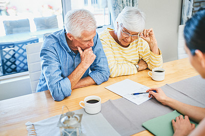 Buy stock photo Shot of a senior couple looking thoughtful while consulting with their financial advisor at home