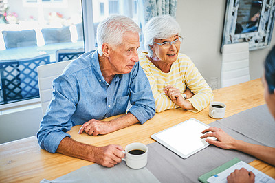 Buy stock photo Shot of a senior couple using a digital tablet while consulting with their financial advisor at home