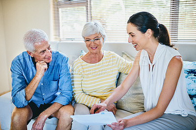 Buy stock photo Shot of a happy senior couple going over paperwork with their financial advisor at home