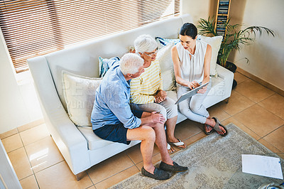 Buy stock photo High angle shot of a senior couple using a digital tablet while consulting with their financial advisor at home