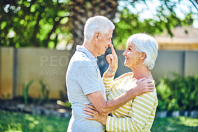 Buy stock photo Shot of a happy senior couple sharing an affectionate moment in their backyard at home