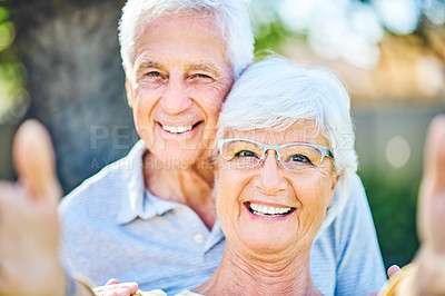 Buy stock photo Shot of a happy senior couple taking selfies together in their backyard at home