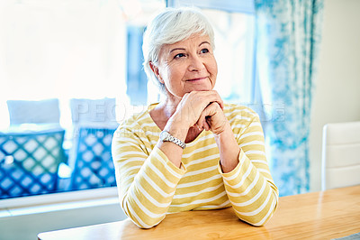 Buy stock photo Shot of a happy senior woman looking thoughtful at home