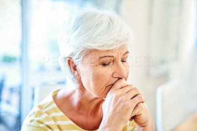 Buy stock photo Shot of a senior woman looking depressed at home