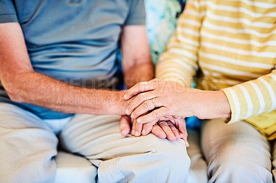 Buy stock photo Cropped shot of a senior couple sitting on the sofa at home and holding hands