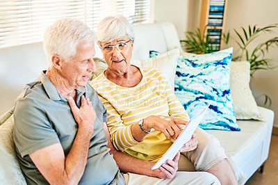 Buy stock photo Shot of a senior couple going through their paperwork together on the sofa at home