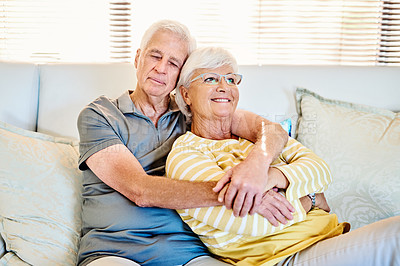 Buy stock photo Shot of a happy senior couple relaxing together on the sofa at home