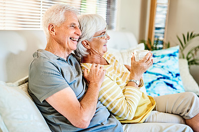 Buy stock photo Shot of a happy senior couple having a relaxing coffee break together on the sofa at home