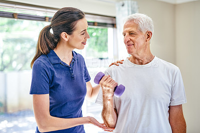 Buy stock photo Shot of a fitness instructor assisting a senior man with some weightlifting exercises