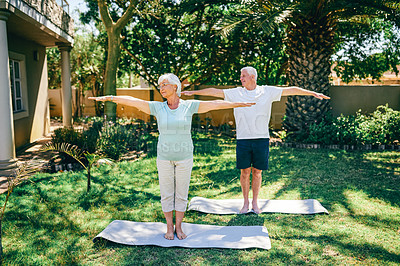 Buy stock photo Shot of a senior couple exercising together outdoors