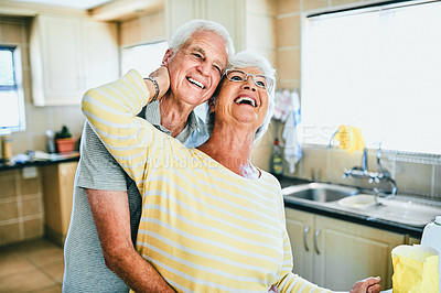 Buy stock photo Shot of an affectionate senior couple in their kitchen at home