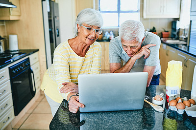 Buy stock photo Shot of a senior couple using a laptop while standing in the kitchen at home