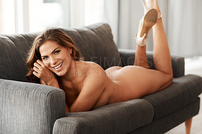 Buy stock photo Full length portrait of a gorgeous young woman smiling while lying naked with stilettos on her couch at home