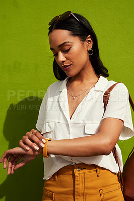 Buy stock photo Cropped shot of an attractive young woman looking at her watch while standing against a green background in the city