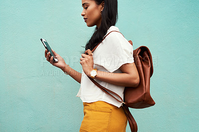 Buy stock photo Cropped shot of an unrecognizable woman standing alone against a blue background and texting while in the city
