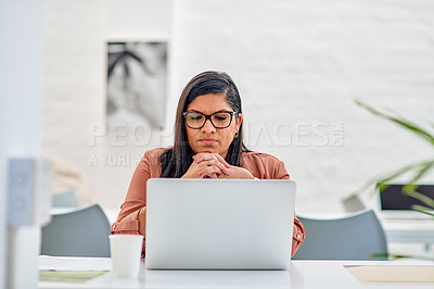 Buy stock photo Cropped shot of an attractive young businesswoman sitting alone in her office and looking contemplative while using her laptop