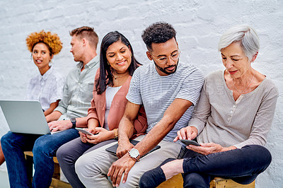 Buy stock photo Cropped shot of a diverse group of businesspeople sitting together and using technology in the office