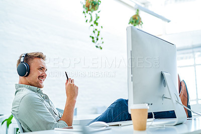 Buy stock photo Cropped shot of a handsome young businessman sitting with his feet up while listening to music through headphones