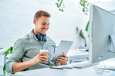 Buy stock photo Cropped shot of a handsome young businessman sitting alone in his office and using a tablet