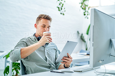 Buy stock photo Cropped shot of a handsome young businessman sitting alone in his office and using a tablet while drinking coffee