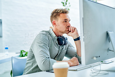 Buy stock photo Cropped shot of a handsome young businessman sitting alone in his office and looking contemplative while using his computer