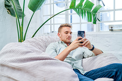 Buy stock photo Cropped shot of a handsome young businessman sitting on a beanbag alone in the office and using his cellphone