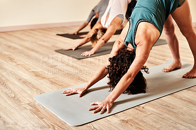 Buy stock photo Shot of a group of young women practicing the downward facing dog pose during a yoga session