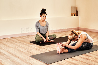 Buy stock photo Shot of a young woman being assisted by a an instructor in a yoga class
