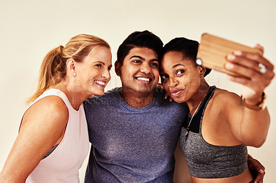 Buy stock photo Shot of a group of young men and women taking selfies in yoga class