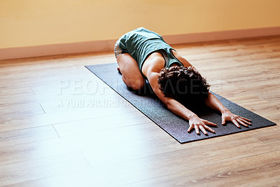 Buy stock photo Shot of a fit young woman practicing the child's pose during a yoga session
