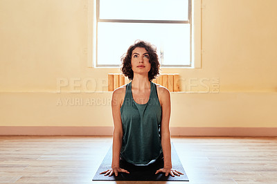 Buy stock photo Shot of a young woman practicing the cobra pose during a yoga session